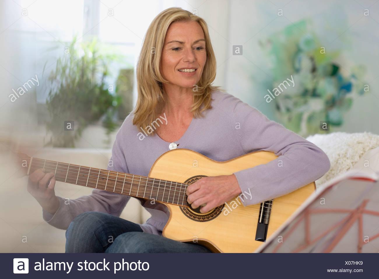 Woman playing guitar - Stock Image