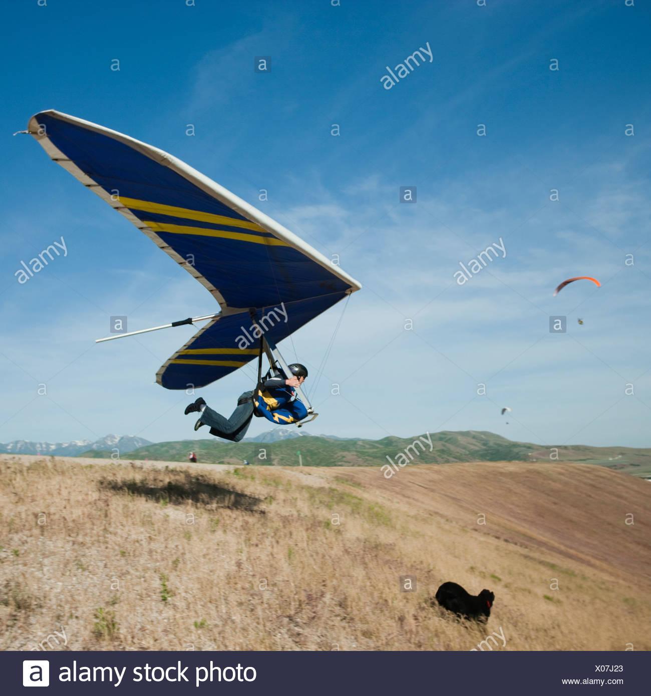 USA, Utah, Lehi, young man taking off with hang glider - Stock Image