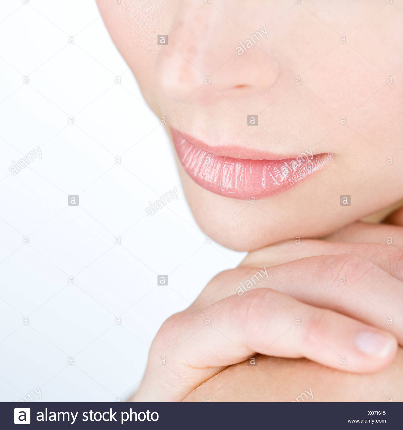 A cropped portrait of woman with her hand on her shoulder - Stock Image