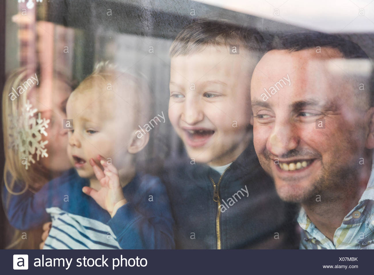 Mother, father and sons looking out of window, squashing faces against glass - Stock Image