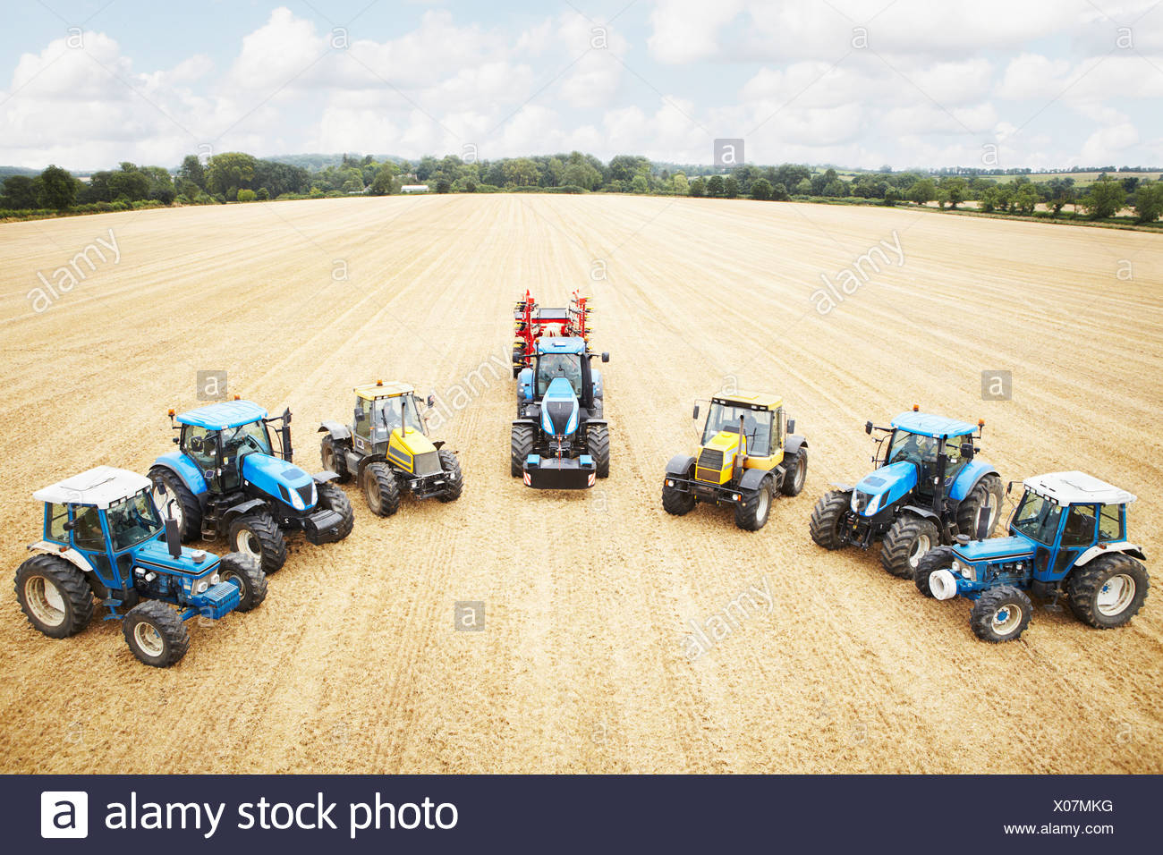 Tractors parked in tilled crop field - Stock Image