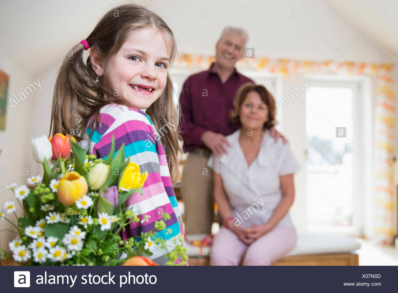 Granddaughter handover bouquet to her grandmother and grandfather in background - Stock Image