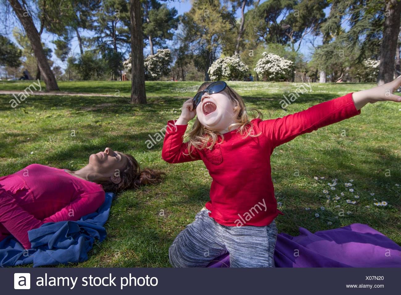 three years old blonde child, with red shirt, sitting on knees in green grass in park, next to mother sleeping, with big adult woman sunglasses - Stock Image
