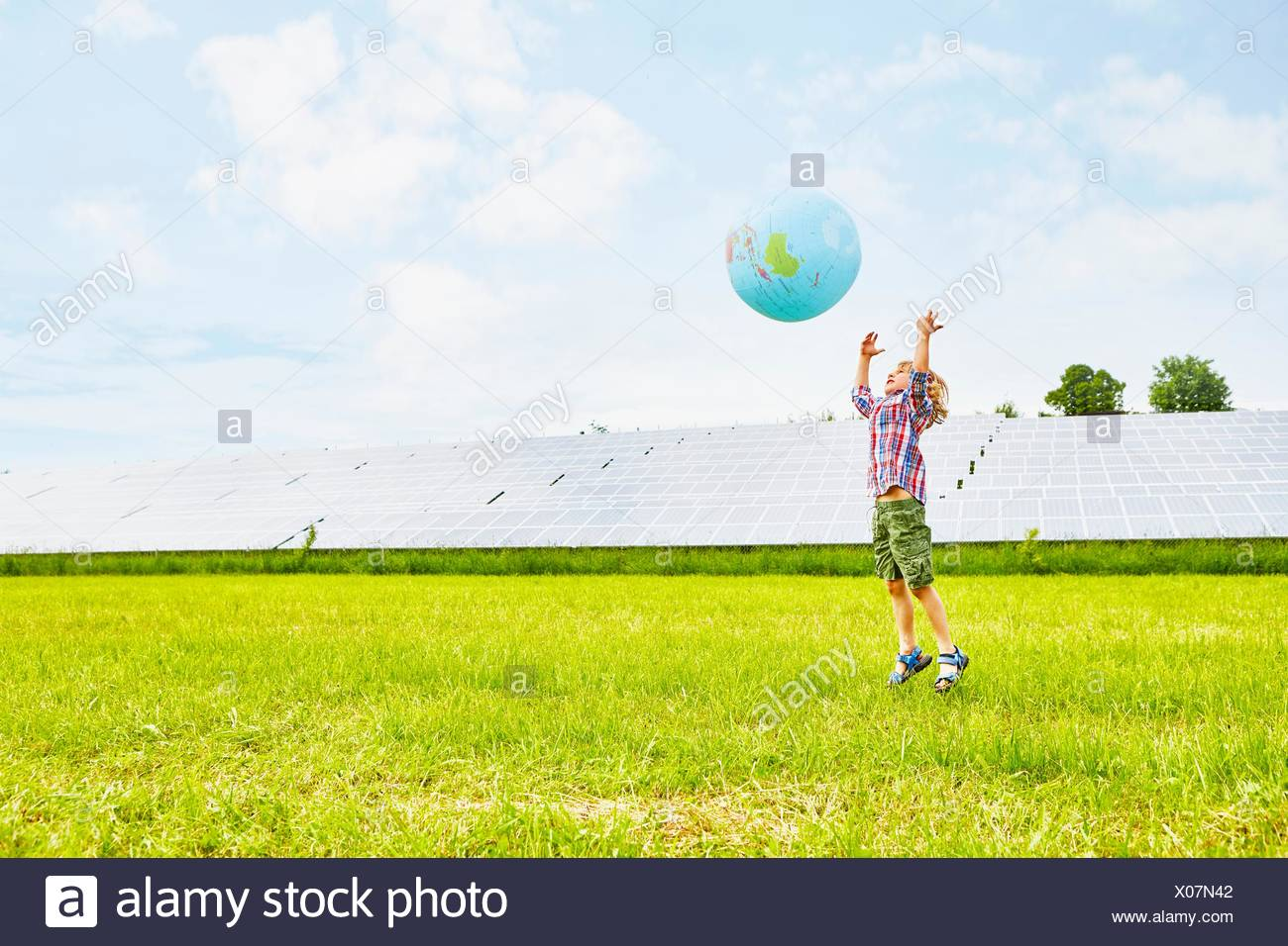 Young boy playing with inflatable ball, on field, next to solar farm - Stock Image