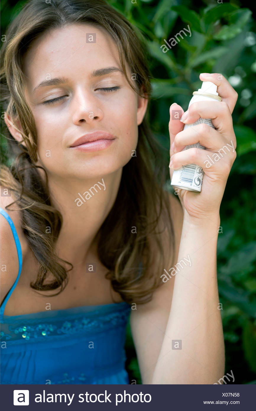A DayYourself: Female long brunette hair tied back loosely wearing blue top holding small atomiser spray to side of face,head - Stock Image