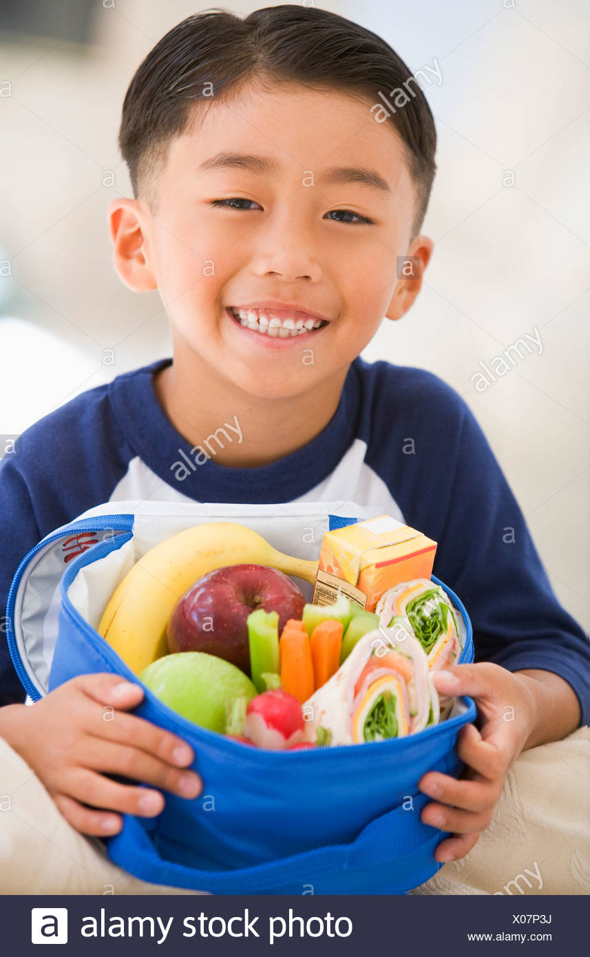 Young boy indoors with packed lunch smiling - Stock Image