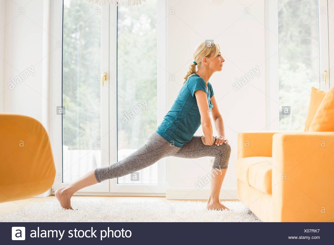 Mature woman doing lunge stretch exercise in living room - Stock Image
