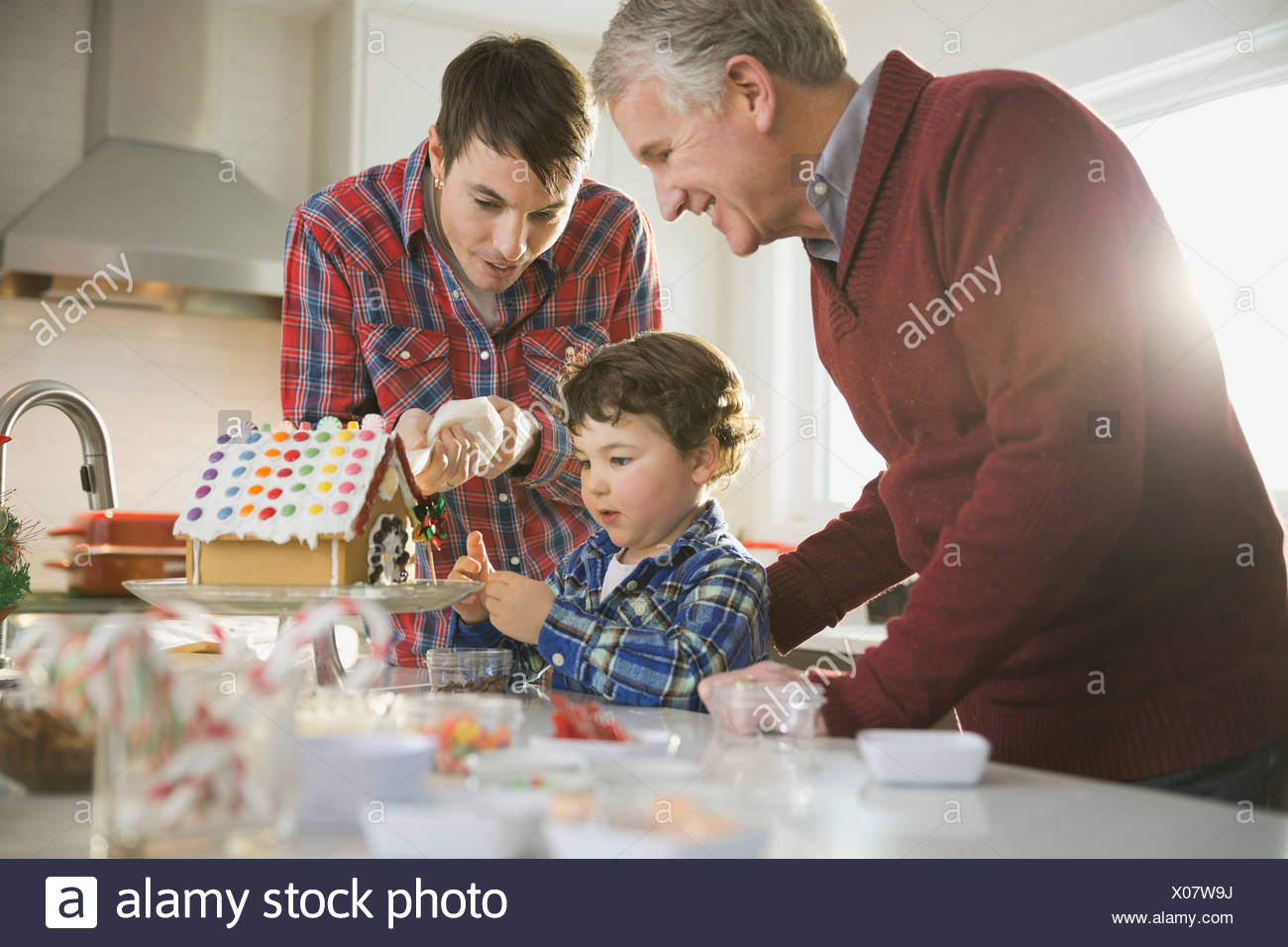 Three generation males decorating gingerbread house at Christmas - Stock Image