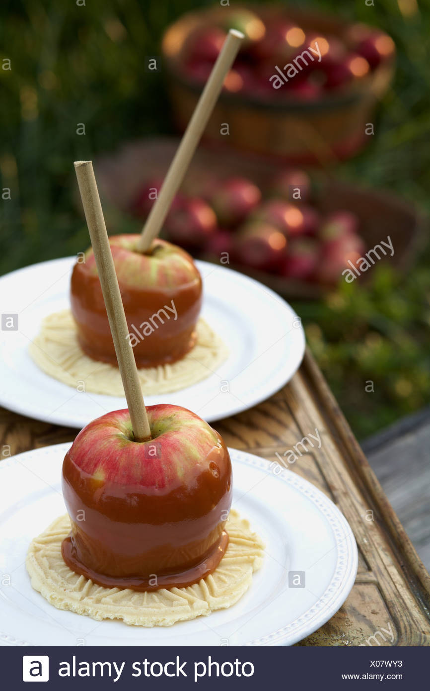 Two toffee apples on plates - Stock Image