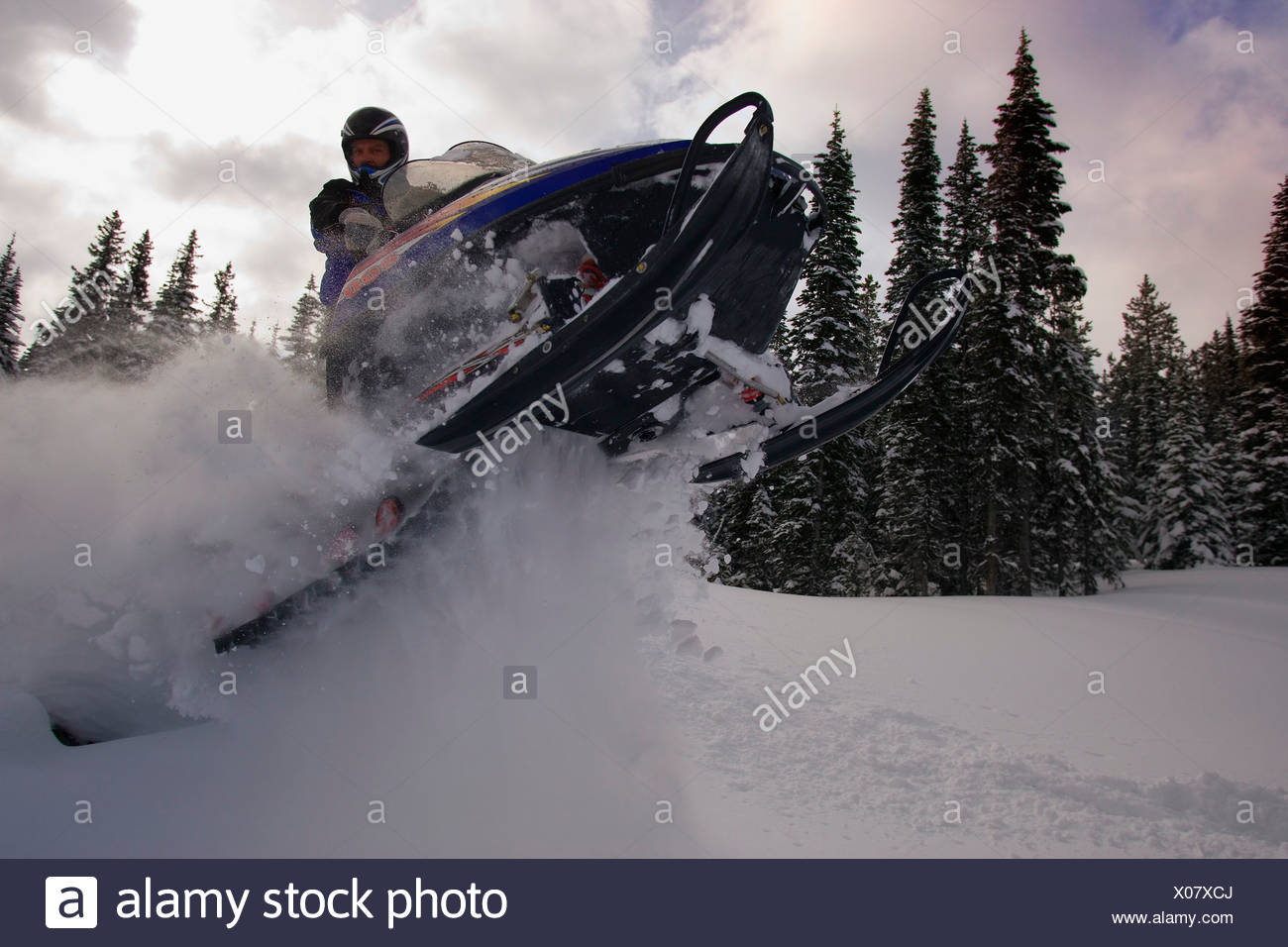 Man jumping a snowmobile - Stock Image