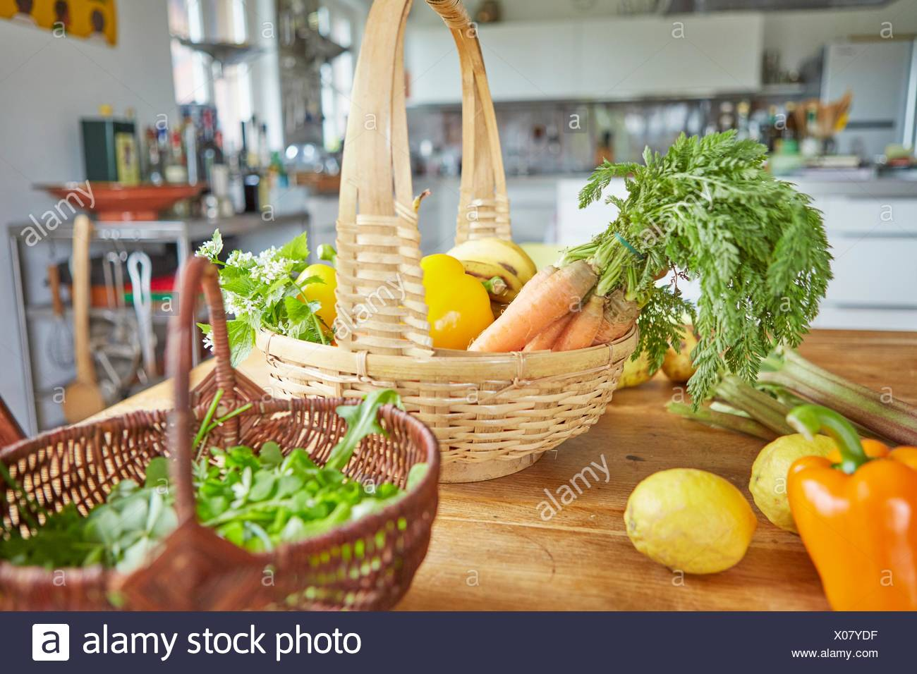Still life of garden produce, in baskets on table in kitchen - Stock Image