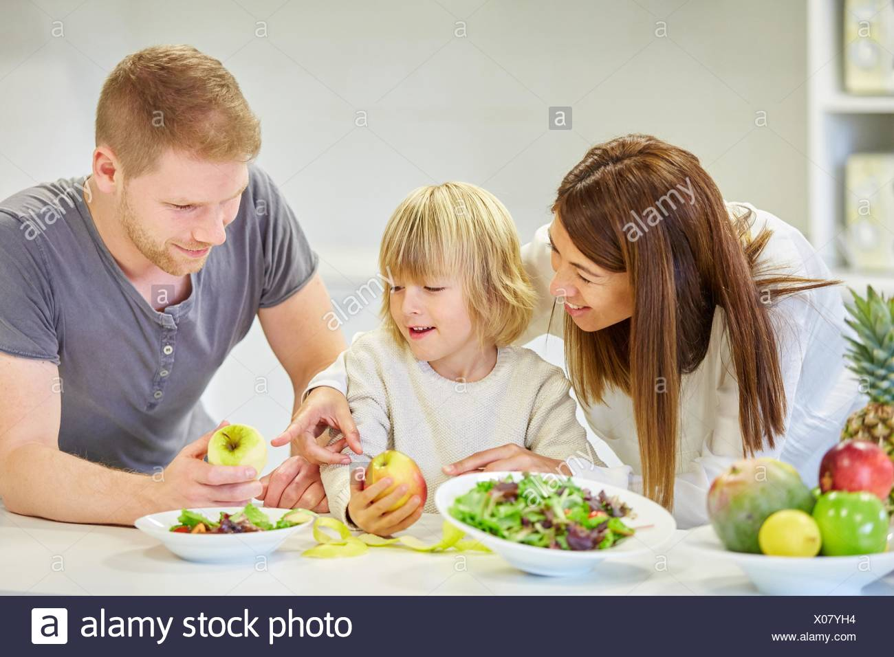 Family in the kitchen. Parents and son. Healthy eating. Healthy growth. Eating an apple. - Stock Image