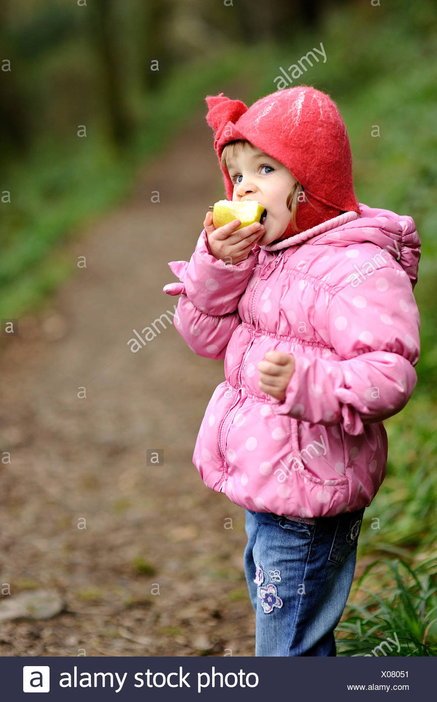 Girl eating an apple outdoors - Stock Image