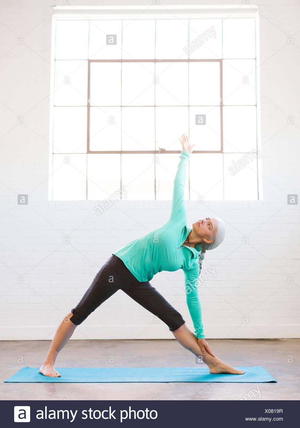 Senior woman practicing yoga on mat Stock Photo