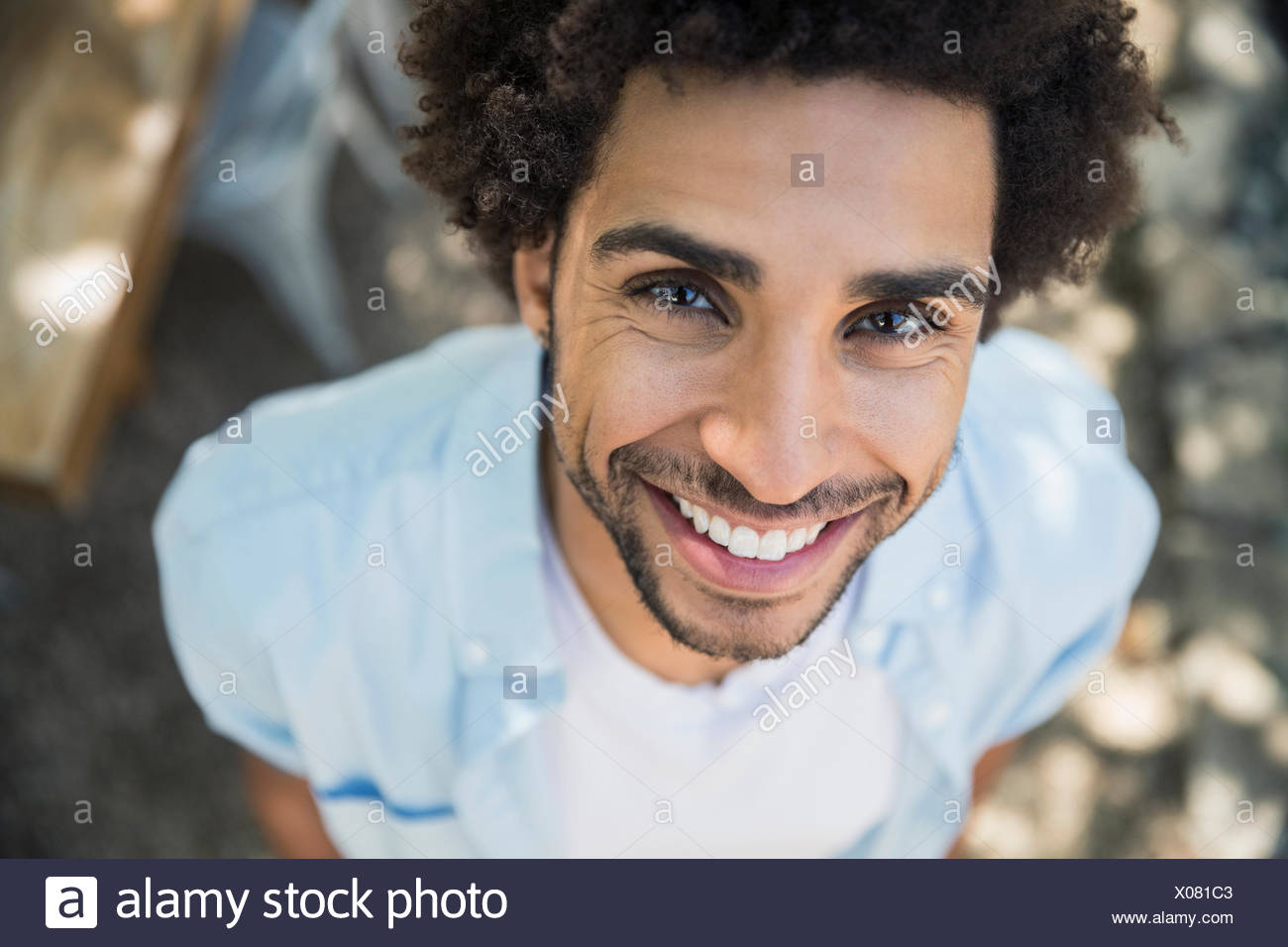 High angle portrait smiling man curly hair - Stock Image