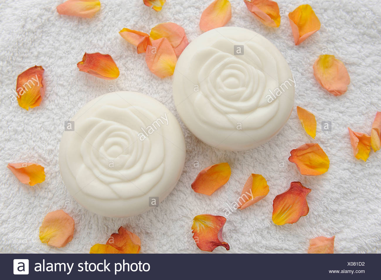 Two white round bars of soap a rose shaped pattern on the top of