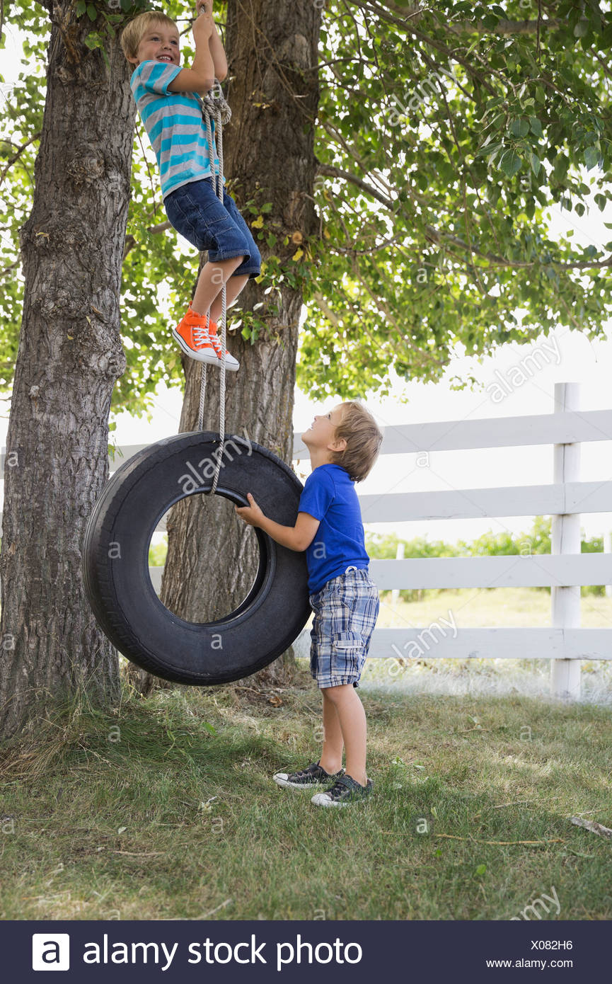 Playful boys playing on tire swing Stock Photo
