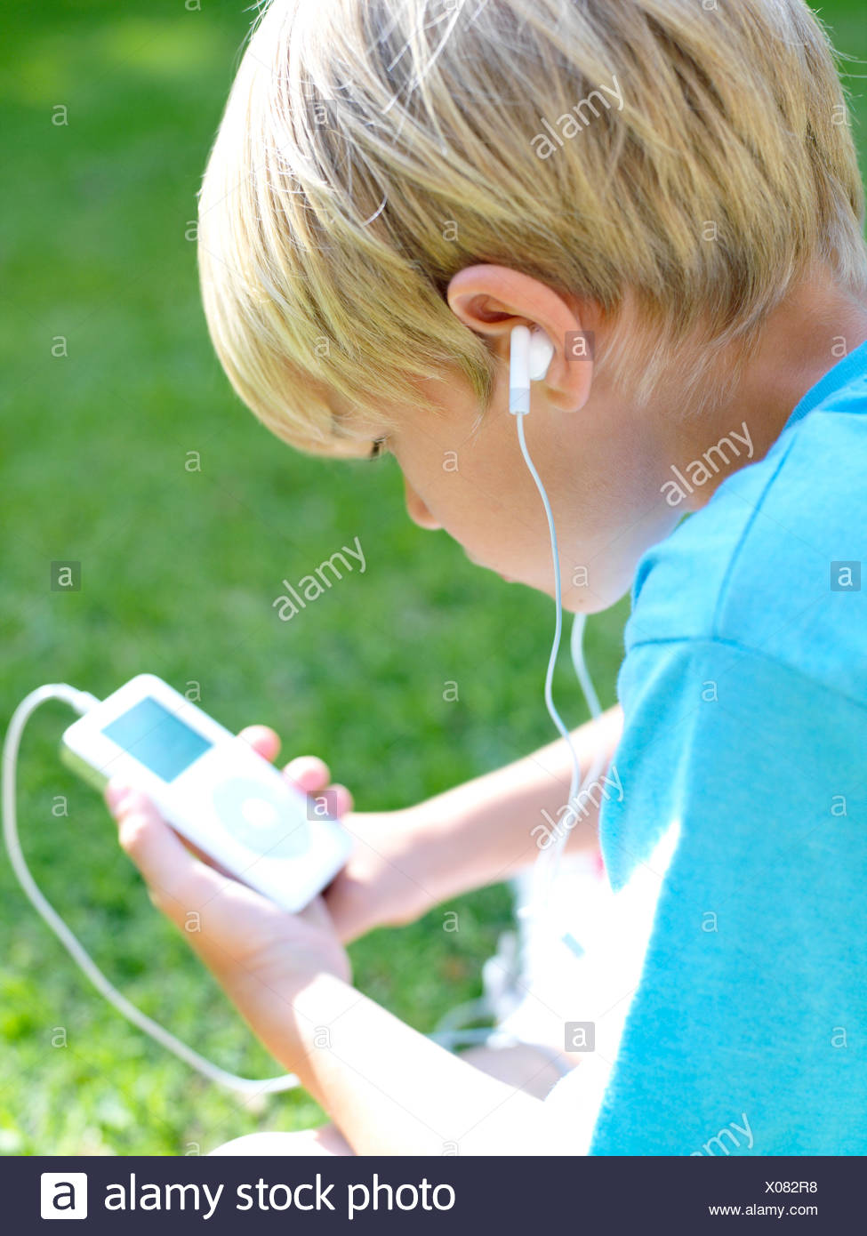 Boy (6-8) with MP3 player, rear view - Stock Image
