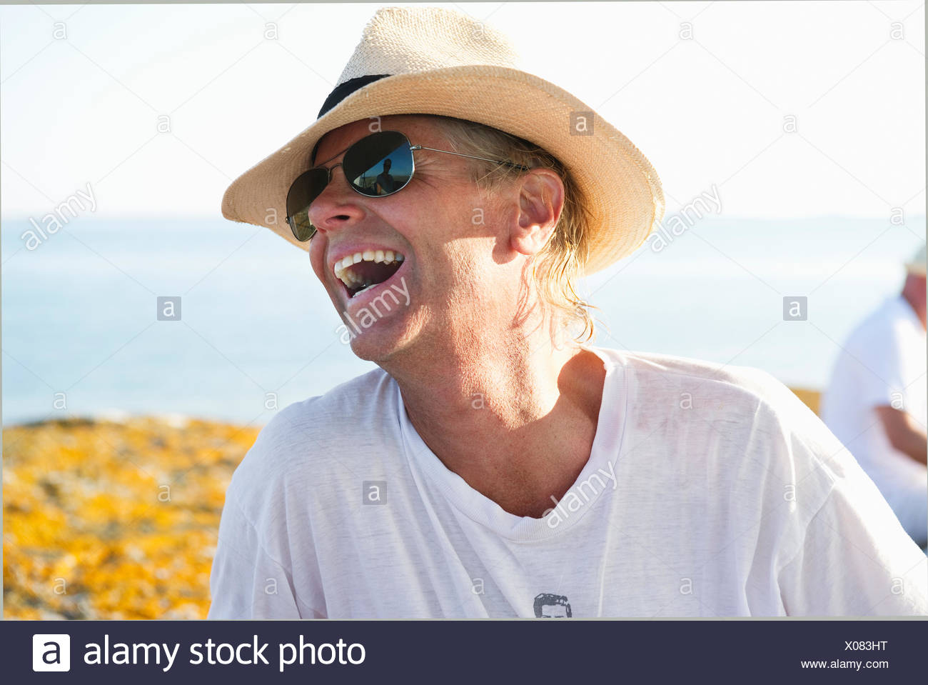 Portrait of smiling man wearing sunglasses and straw hat - Stock Image