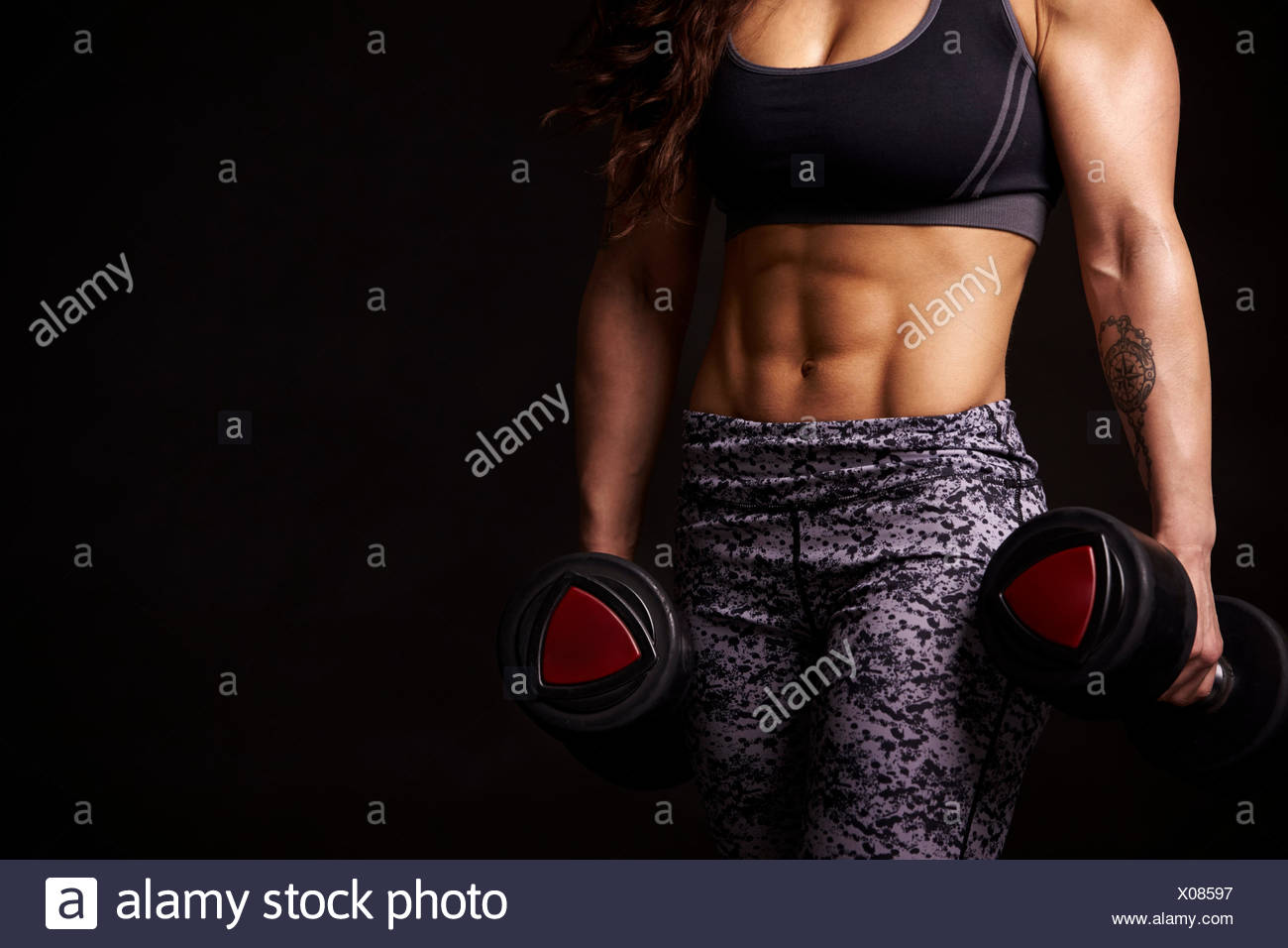 Muscular woman working out with dumbbells, mid-section crop - Stock Image