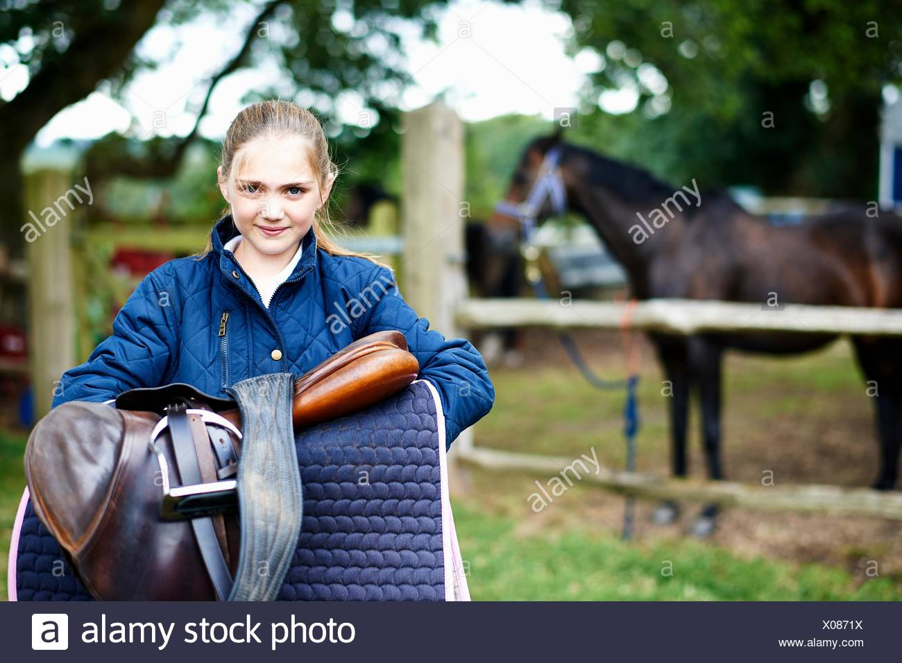 Girl horseback rider carrying saddle - Stock Image