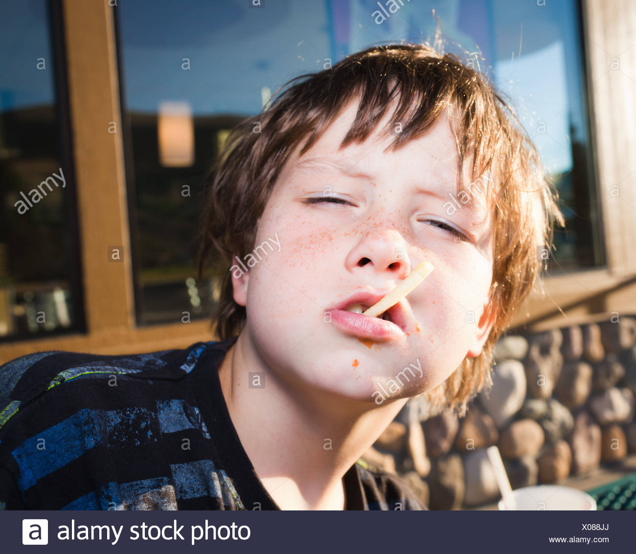 Boy being defiant with junk food - Stock Image