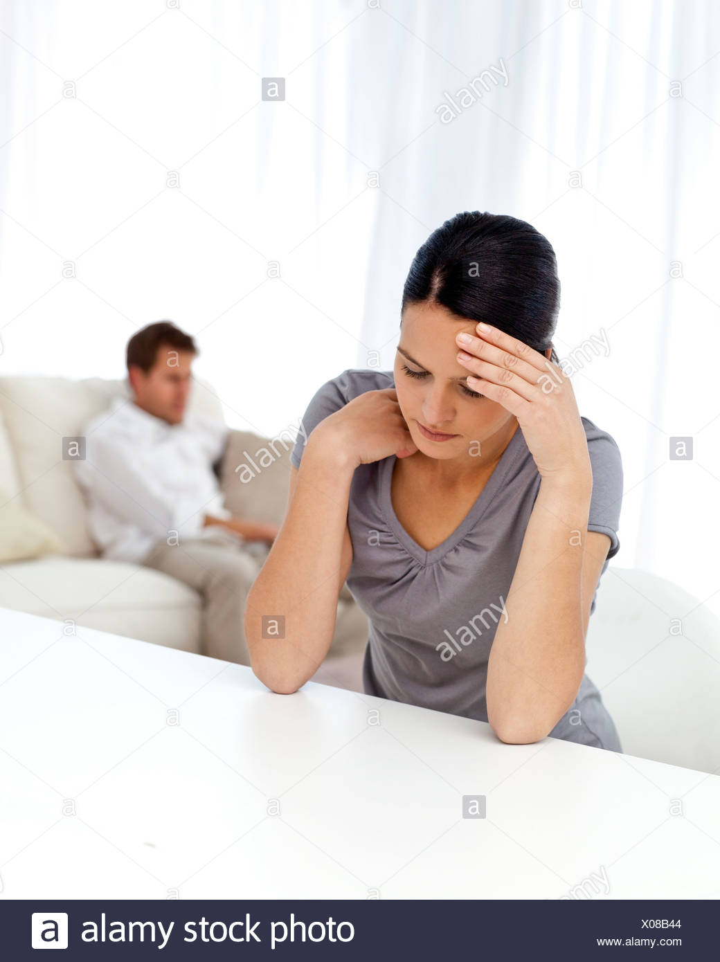 Worried woman sitting at a table while her boyfriend is lying on the sofa - Stock Image
