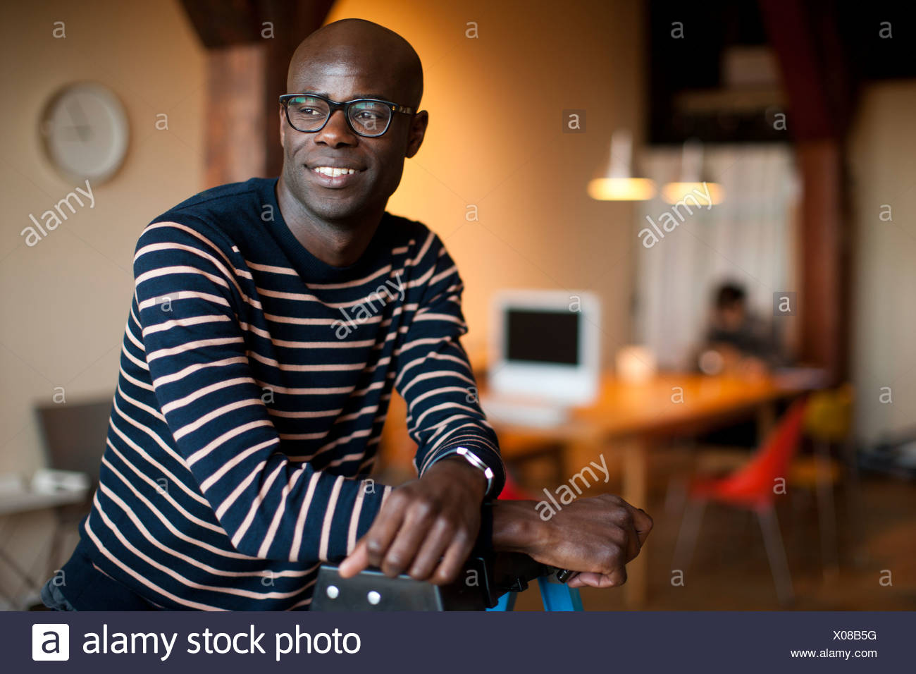 Smiling man leaning on luggage - Stock Image