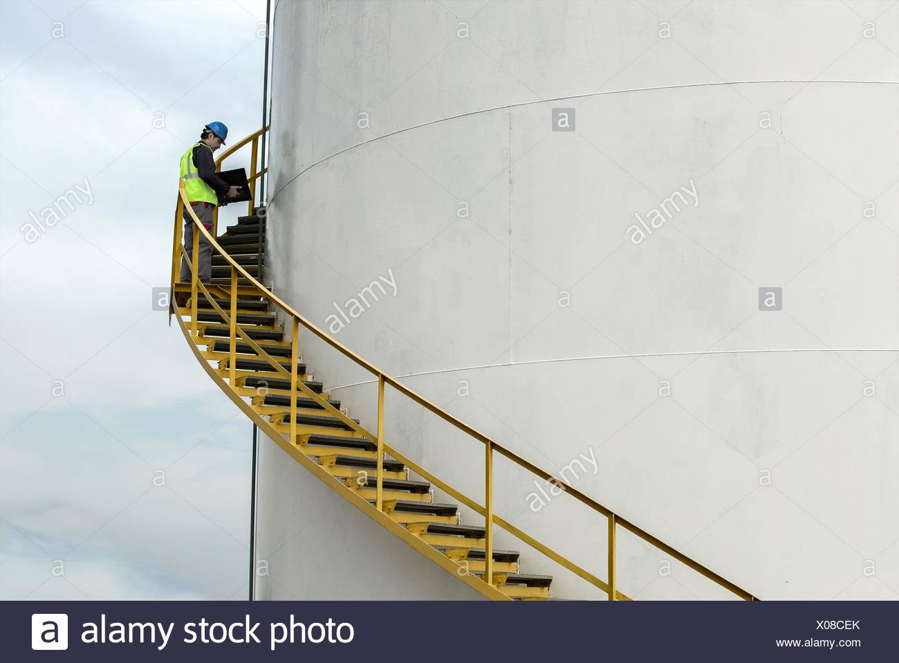 Industrial worker on stairs checking oil storage tank - Stock Image