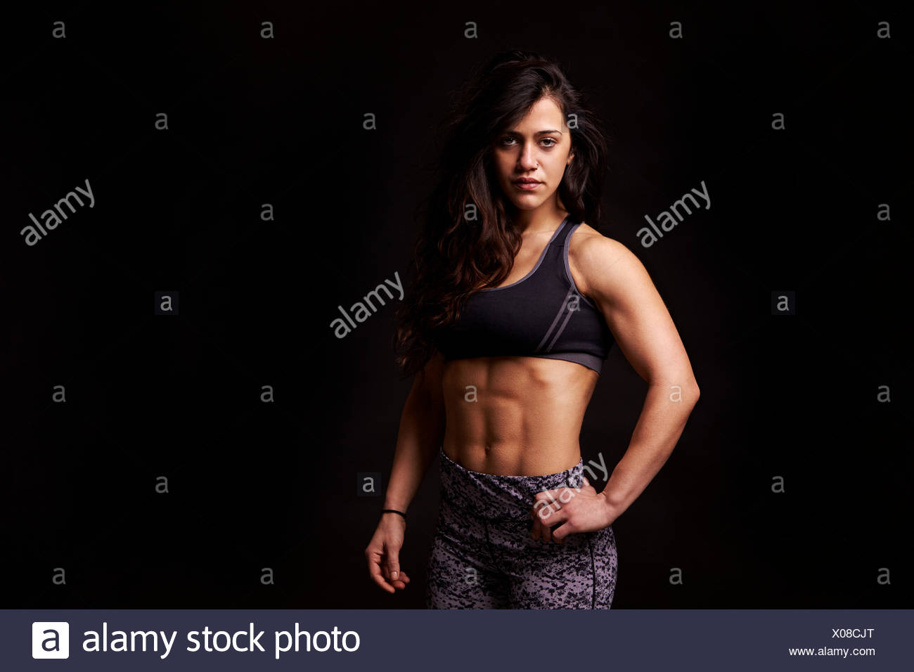Waist up portrait of muscular dark haired young woman - Stock Image