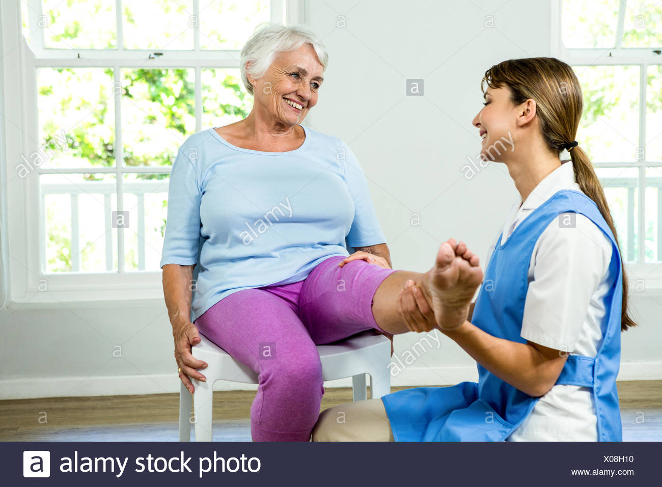Happy nurse assisting aged woman - Stock Image