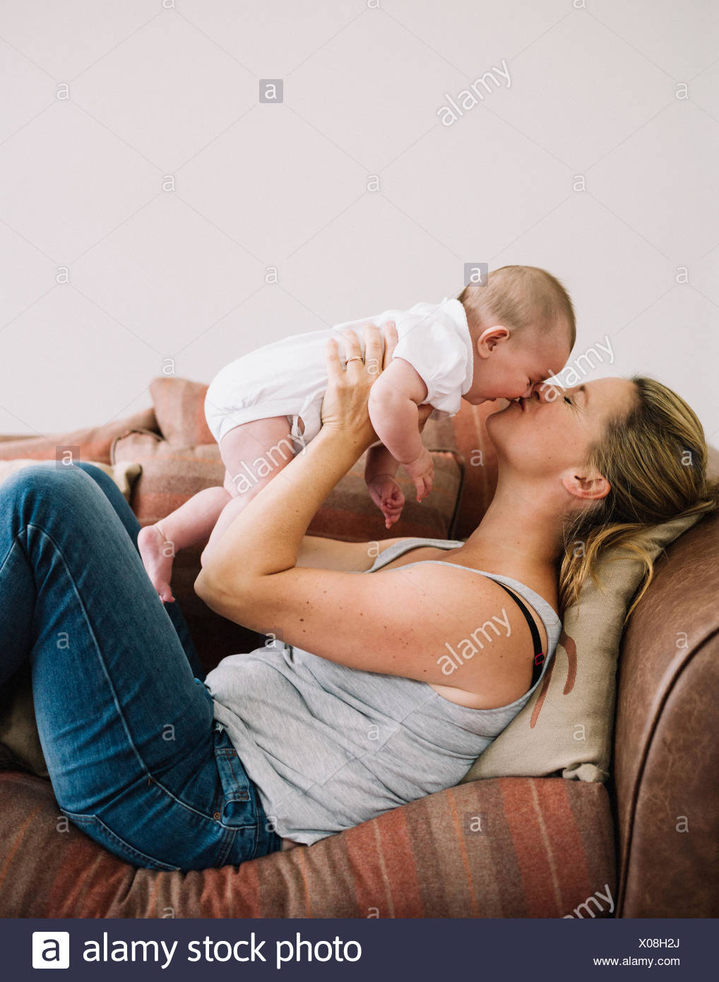 A woman lying on a sofa playing with a baby girl, kissing her cheek. - Stock Image