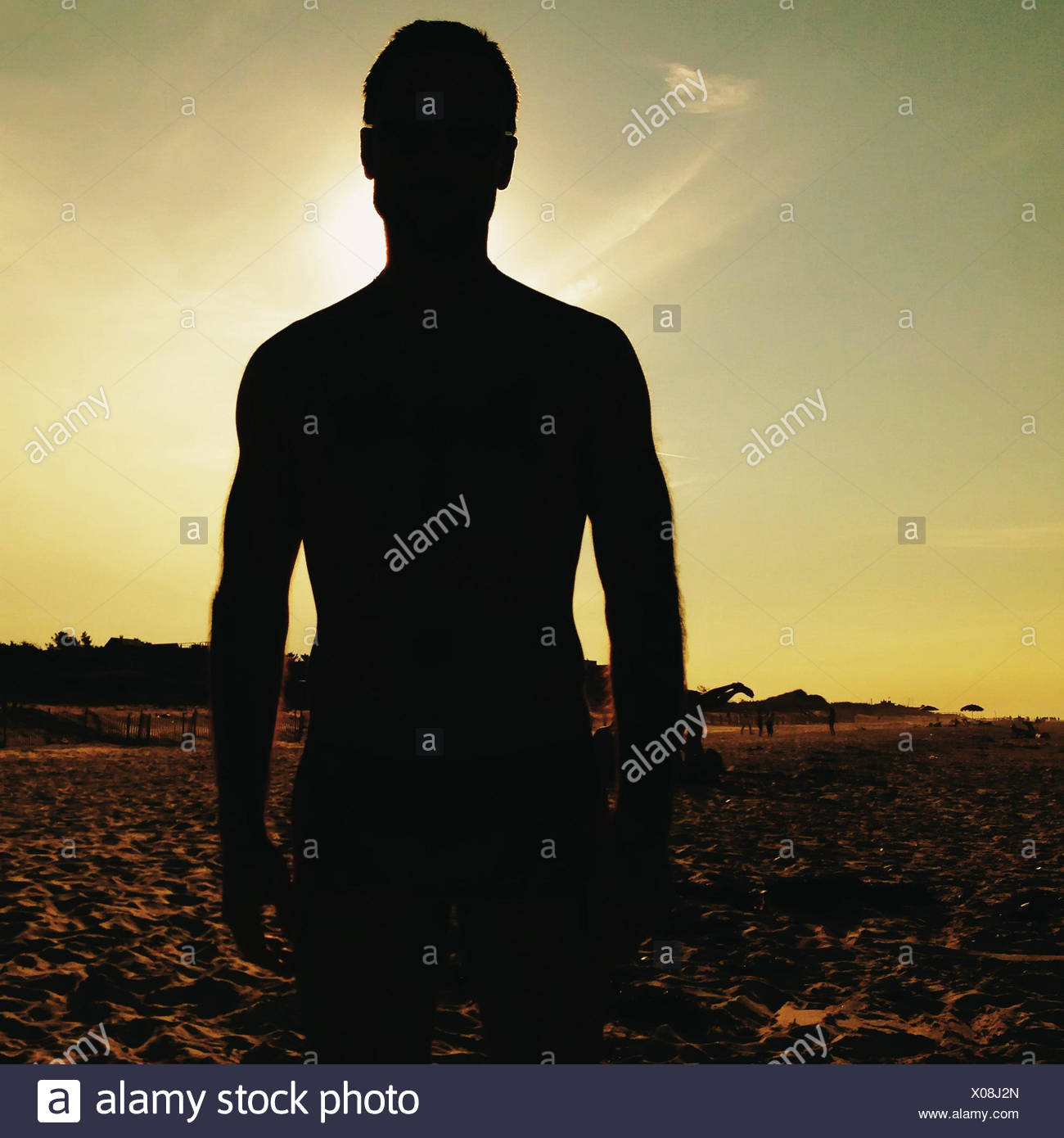 Silhouette of a man standing on beach - Stock Image