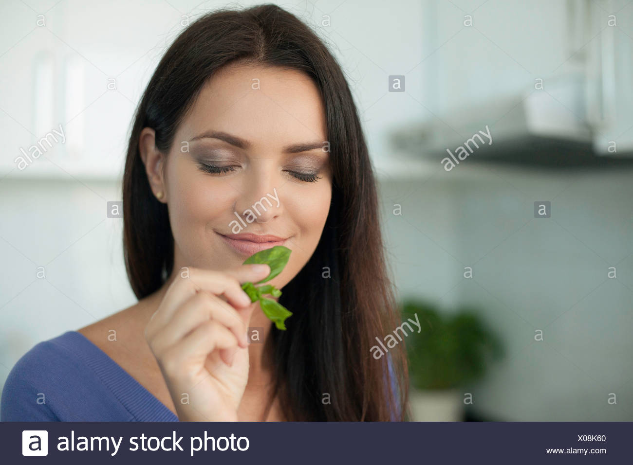 Portrait of young woman smelling basil - Stock Image