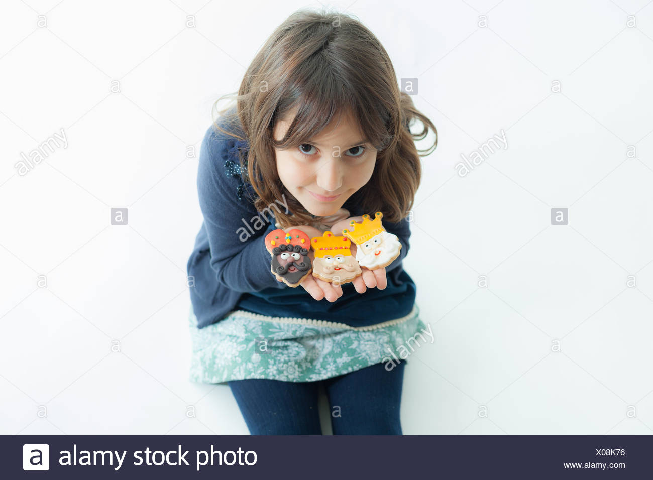 Girl (6-7) with cookies on white background - Stock Image