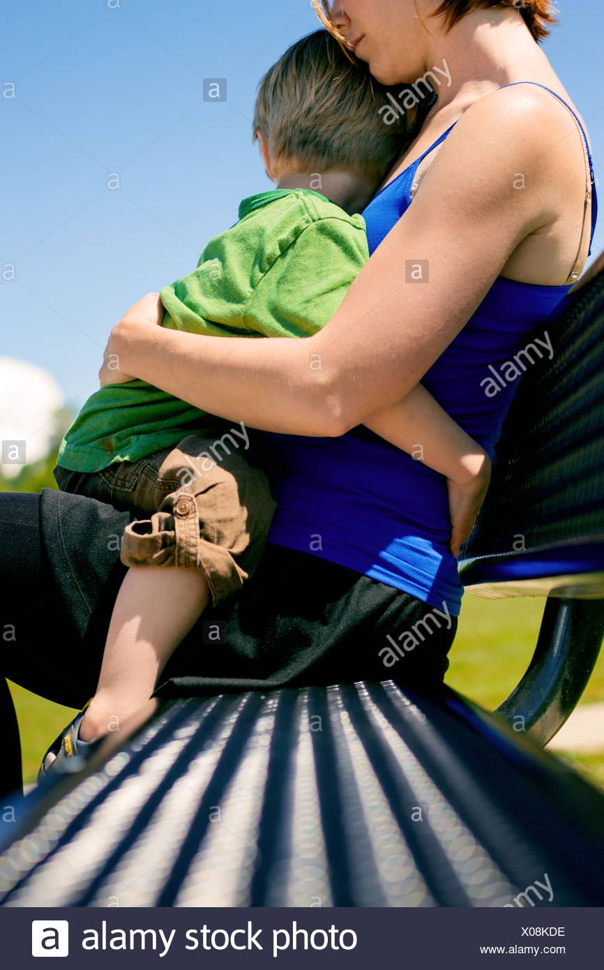 Close-up of a woman sitting on a bench holding her son - Stock Image