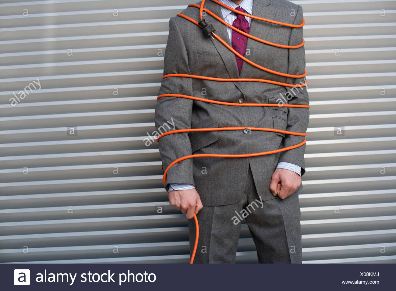 Businessman tied up with power cord - Stock Image
