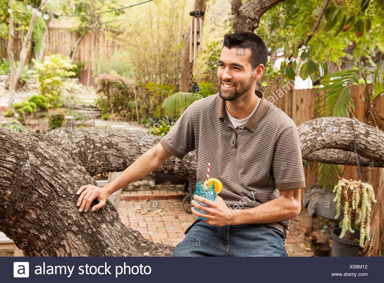 Man sitting on branch in garden having a drink - Stock Image