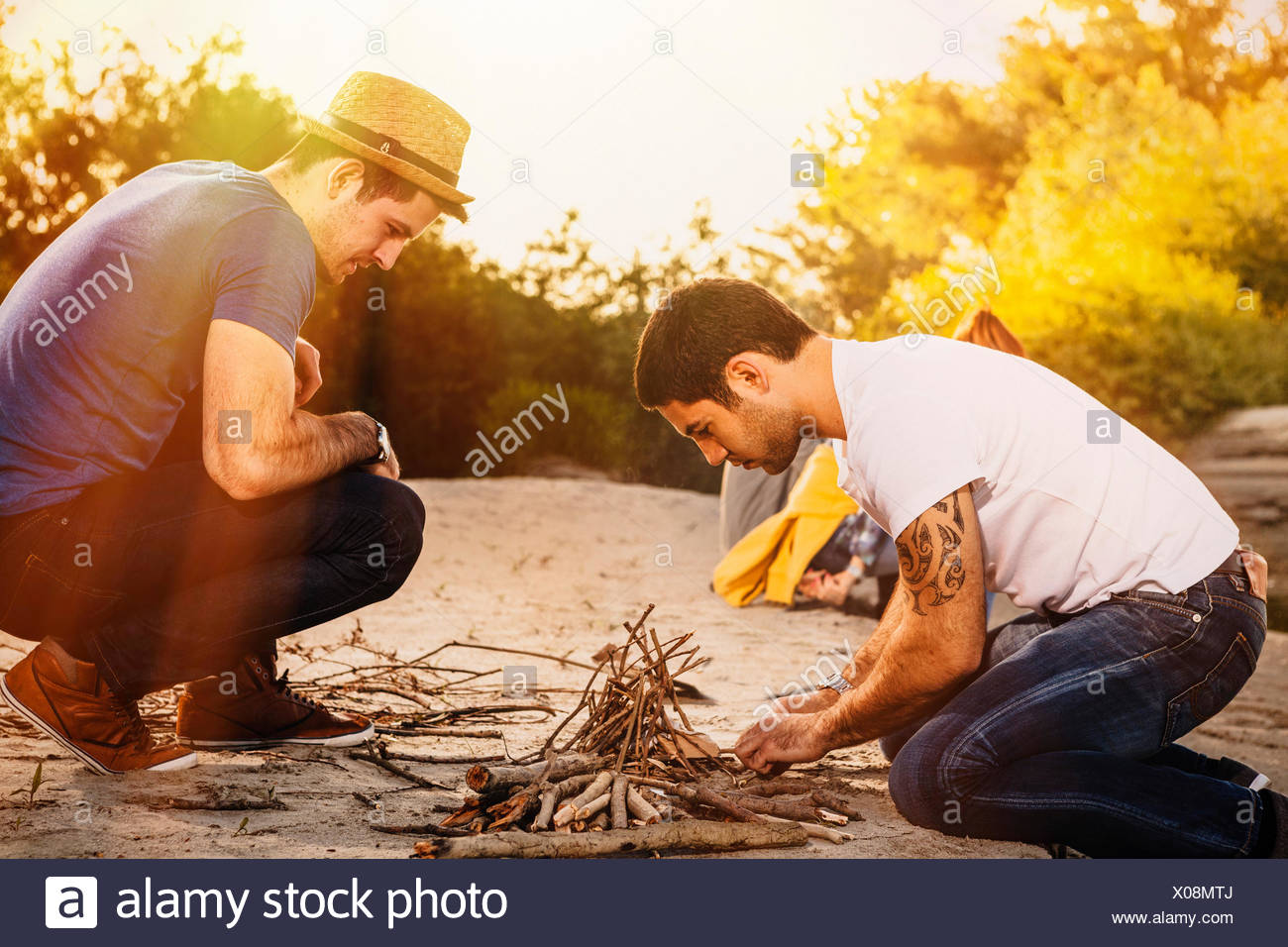 Two friends arranging firewood for a campfire,  Osijek, Croatia - Stock Image
