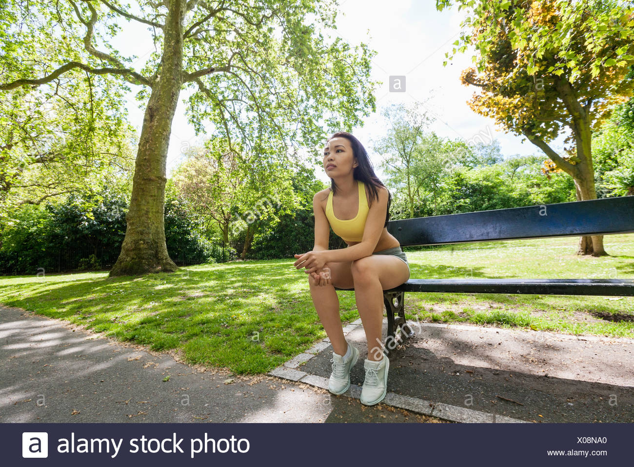 Full length of tired fit woman sitting on beach while exercising in park - Stock Image