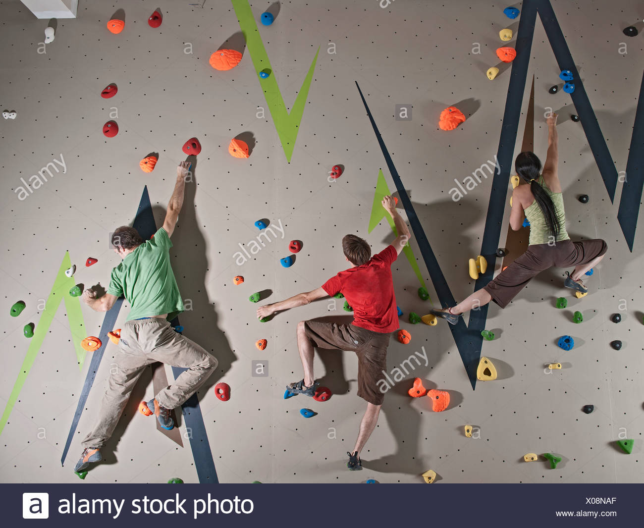 Three adults bouldering on climbing wall - Stock Image