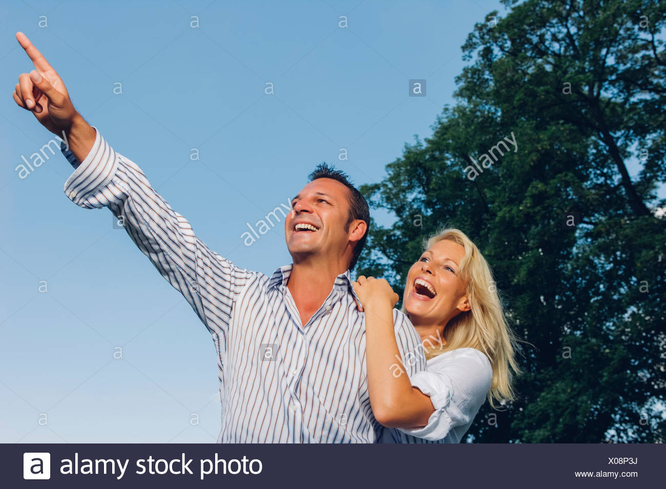 Laughing couple watching something in nature - Stock Image