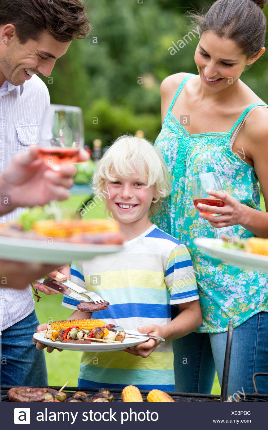 Portrait of smiling boy holding plate of barbecue - Stock Image