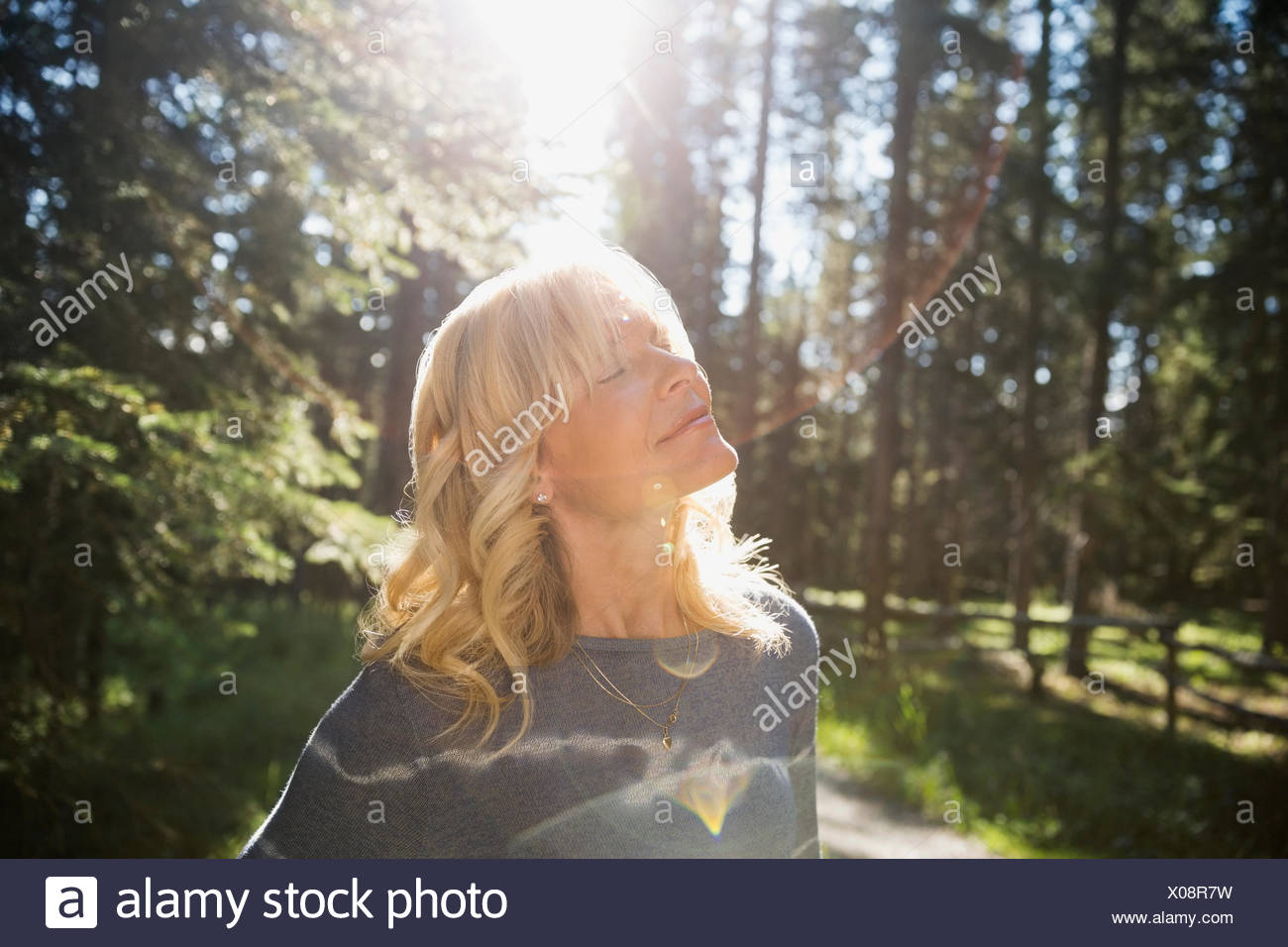 Serene blonde woman eyes closed in sunny woods - Stock Image