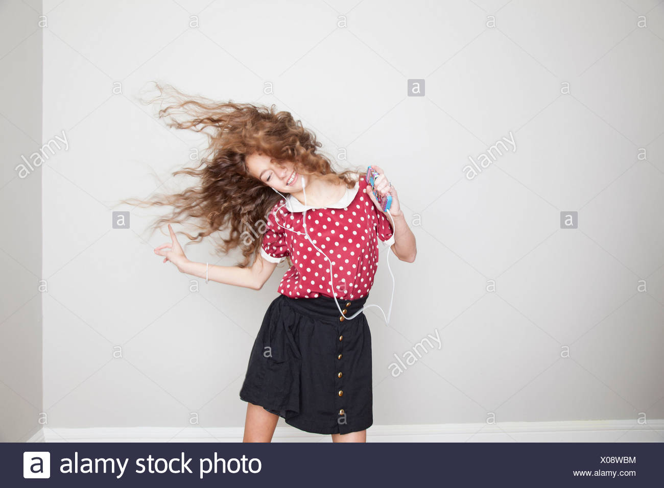Girl wearing headphones, dancing and holding mp3 player - Stock Image