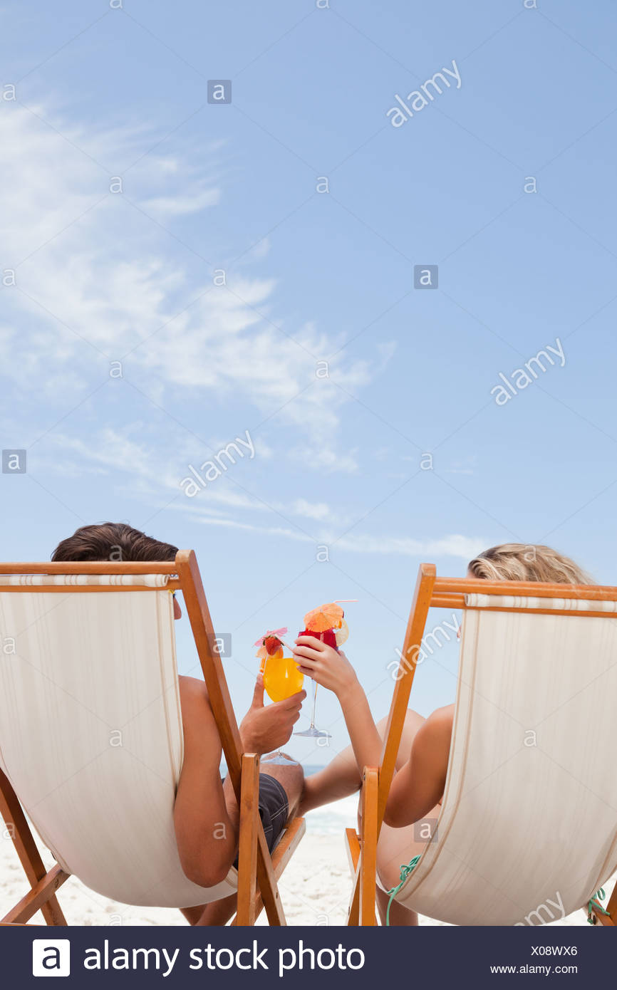 Rear view of a young couple clinking their glasses together - Stock Image