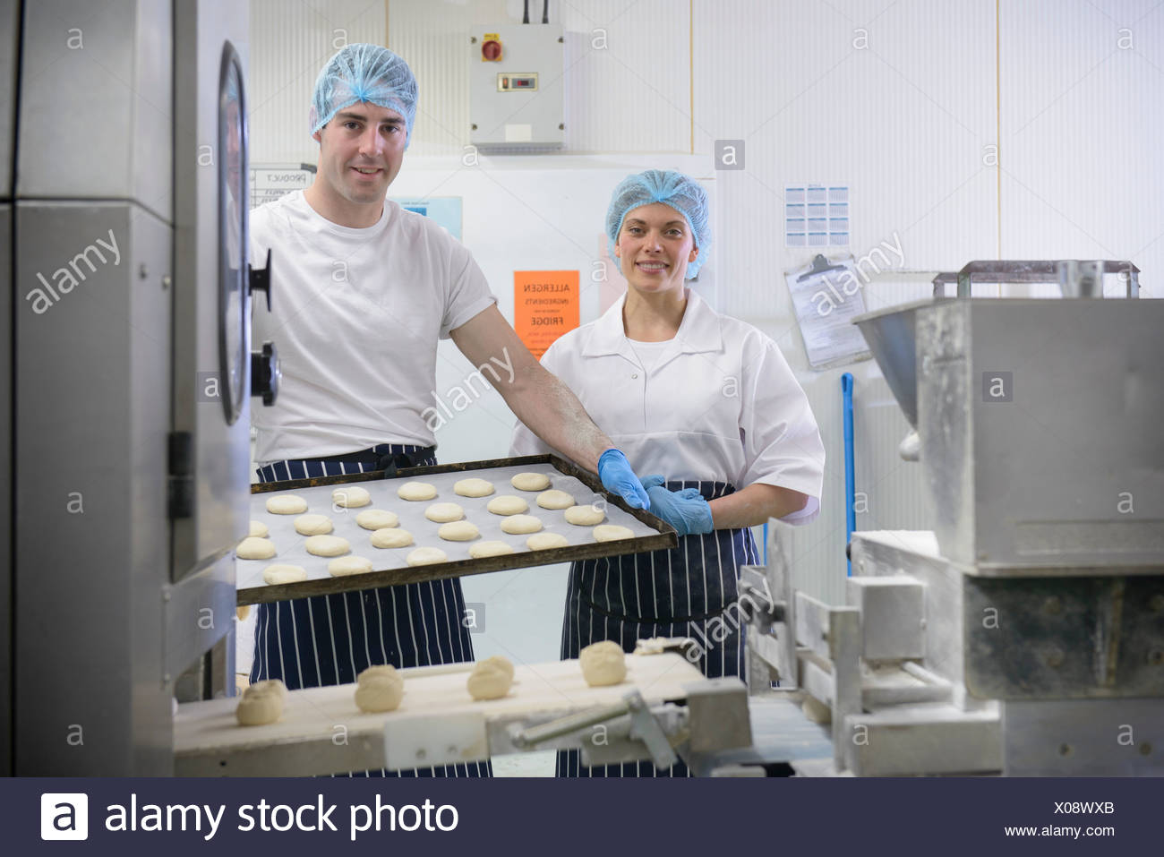 Bakers holding tray of prepared dough, portrait - Stock Image