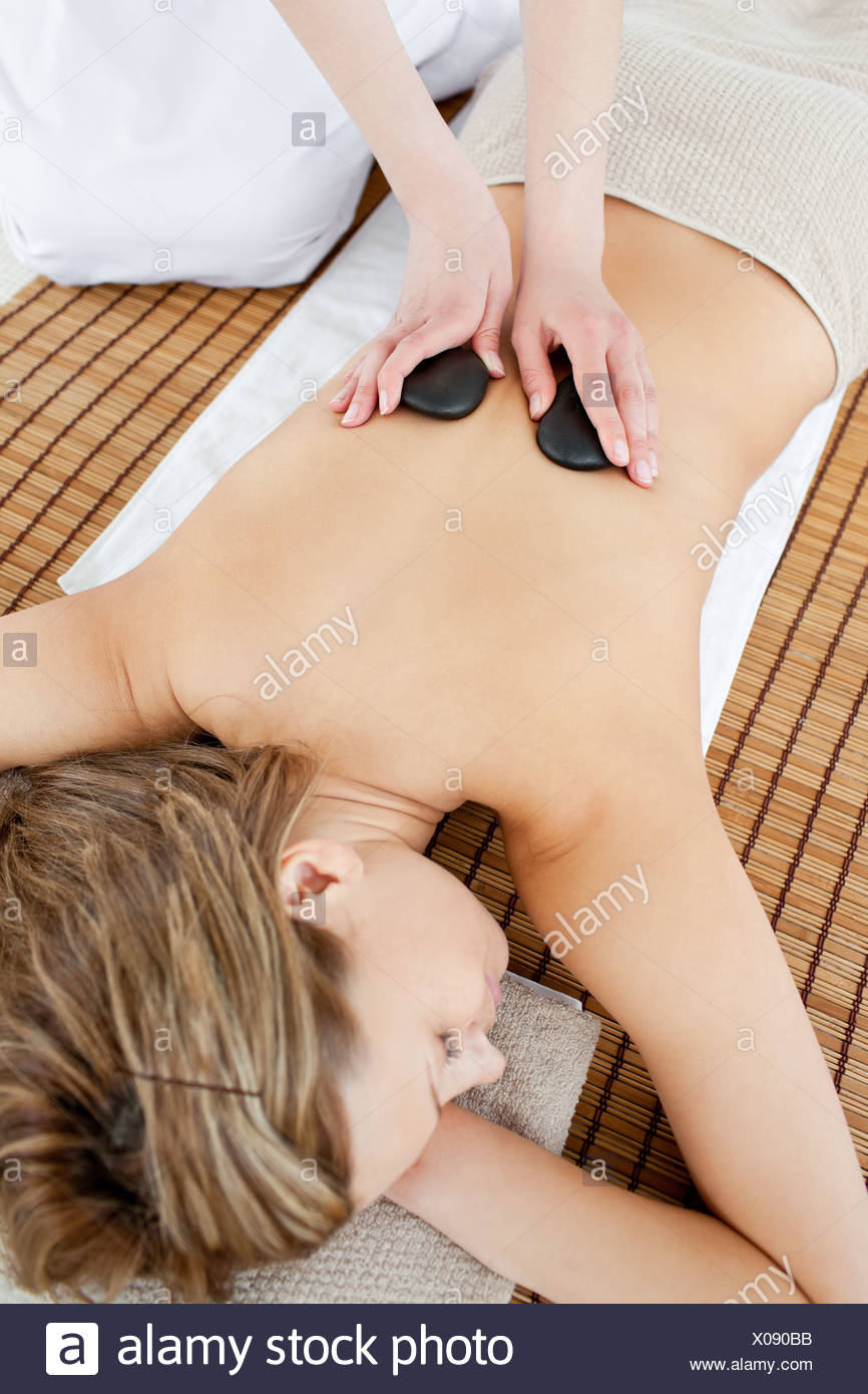 Pretty woman lying on a massage table having a stone therapy - Stock Image