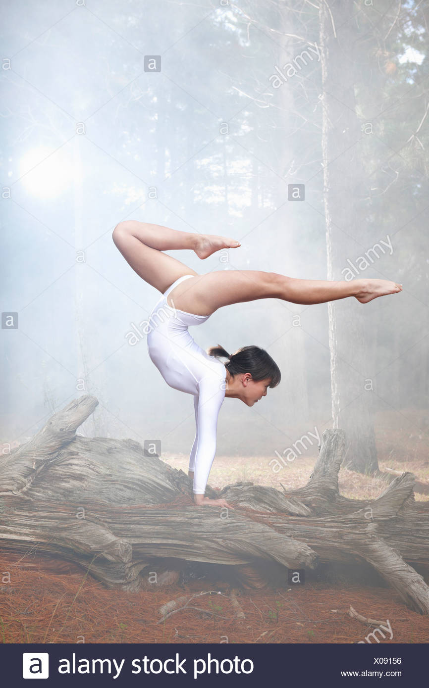 Dancer posing on log in forest - Stock Image