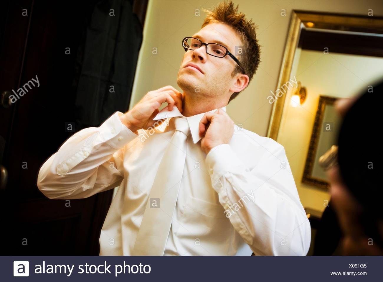 Groom, man putting on tie - Stock Image